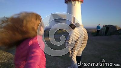 Ung kvinna med hennes stora familj som leder hennes make som går in mot den steniga nordliga stranden lager videofilmer