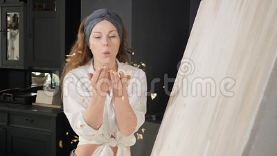 Ung kvinna som blåser hand i hand med bestruket gyllene papper i långsam rörelse Konstskola, kreativitet och människobegrepp Shot lager videofilmer