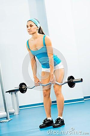 Ung kvinna som gör bodybuilding i idrottshallen