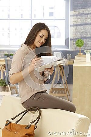 Ung kvinna som kontrollerar post som att få hemmet