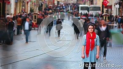 Ung kvinna som poserar, upptagen gata, folk som omkring går, 4K lager videofilmer