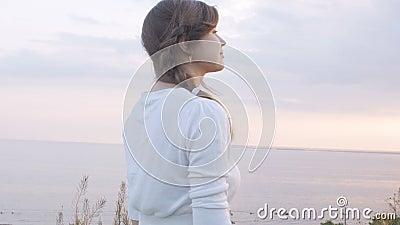 Ung kvinna som ser solnedgången, flickan som går på naturen på en varm afton och tycker om härlig himmel, begreppet av naturen stock video