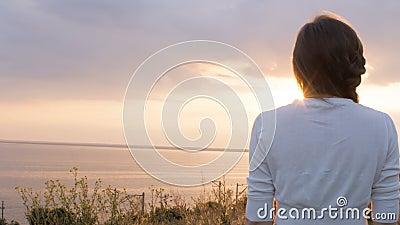 Ung kvinna som ser solnedgången, flickan som går på naturen på en varm afton och tycker om härlig himmel, begreppet av naturen arkivfilmer