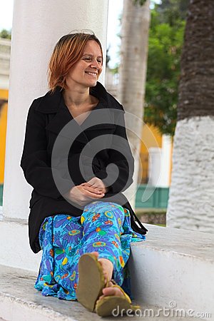 Ung kvinna som sitter på en kolonn