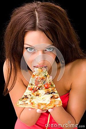 Ung kvinna som äter ett stycke av pizza