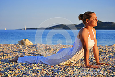 Ung kvinna under yogameditation på stranden