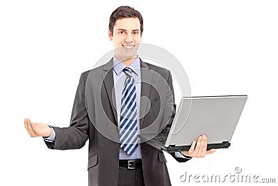 Ung man i en dräkt som rymmer en bärbar dator och gör en gest med handen