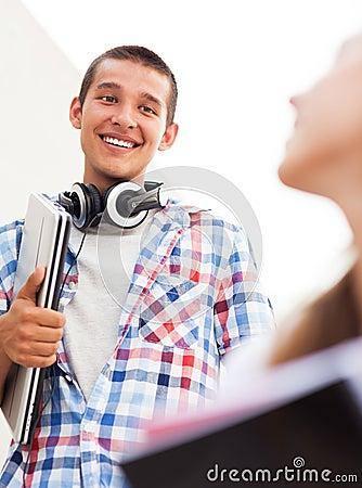 Ung man med bärbar dator och hörlurar