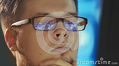 Ung man som arbetar på datoren i mörkt digitalt kontor stock video
