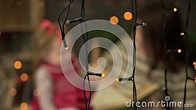 Ung moder med den lilla dotterläseboken hemma Mamma och liten dotter som spelar på bakgrund av girlander blurriness stock video