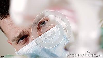 Ung tandläkare i masken tittar på en nära tandvård arkivfilmer