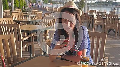Ung vacker kvinna i hatt med mobiltelefon i kafé Begreppet semesterresa lager videofilmer