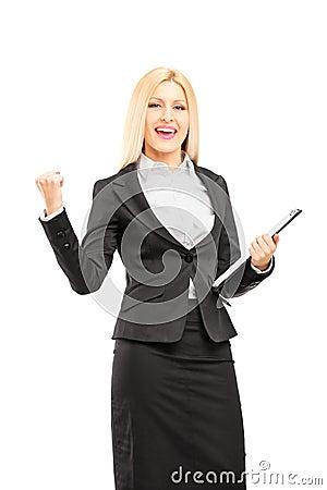 Ung yrkesmässig kvinna som rymmer en skrivplatta och gör en gest happ