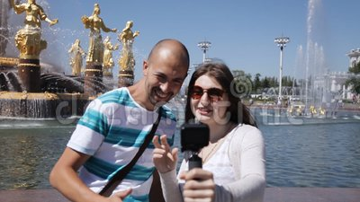 Unga bloggare en man och en kvinna filmar på kameran nära en fontör med gyllene statyer. Europa lager videofilmer