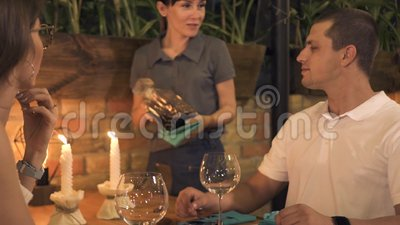 Unga par som sitter på tabellen med stearinljuset medan romantisk matställe i restaurang Man och kvinna som dricker vin på aftone arkivfilmer