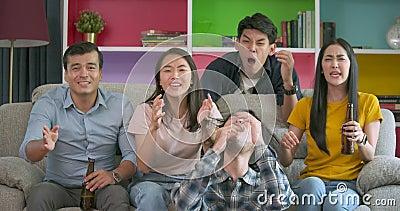 Unga vänner som tillsammans som håller ögonen på fotbollleken på TV är hemmastadd och som är besviken om deras förlorande match f arkivfilmer