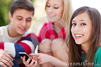 Ungdomar med den mobila telefonen