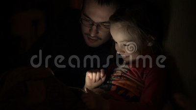 Ungt barnflicka med fadern som spelar leken på mobiltelefonen i mörkt rum, arkivfilmer
