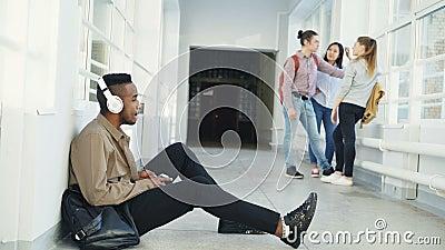 Ungt stiligt afrikansk amerikanstudentsammanträde på golv i den vita korridoren med hörlurar på huvudet som lyssnar till musik arkivfilmer