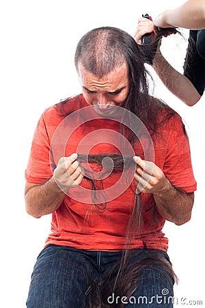 Unhappy bald man holding his long hair