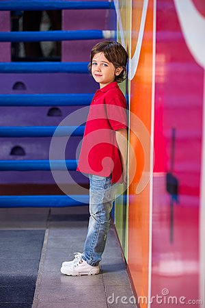 Unhappy Boy Standing Against Wall