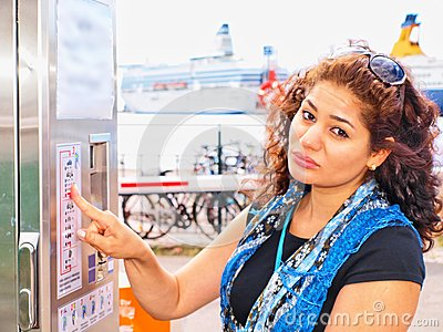 Unhappy brunet at ticket vending machine