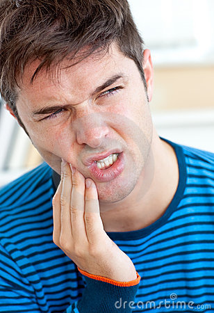 Unhappy caucasian man having a toothache at home