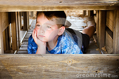 Unhappy child hiding and sulking
