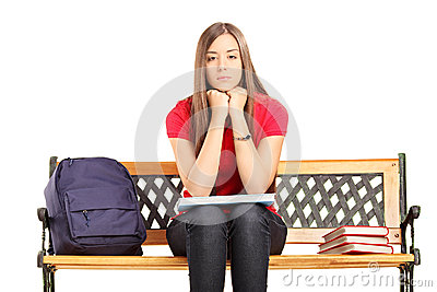 Unhappy female student sitting on a wooden bench