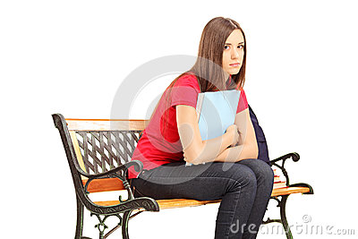 Unhappy female student sitting on a wooden bench with notebook