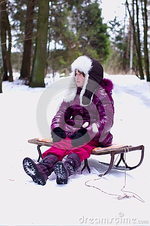 Unhappy kid girl alone in winter forest