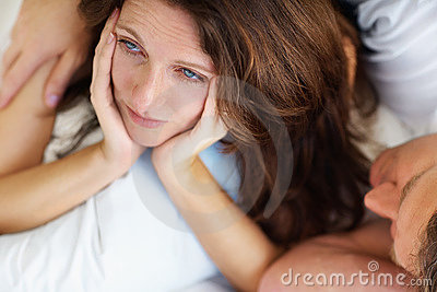 Unhappy lady having problems in bed with husband