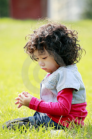 Unhappy little girl on the grass