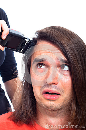 Unhappy man being shaved with hair trimmer
