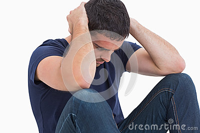 Unhappy man with head in hands sitting on floor