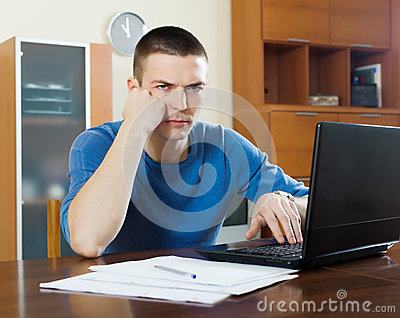 Unhappy man with laptop and  documents