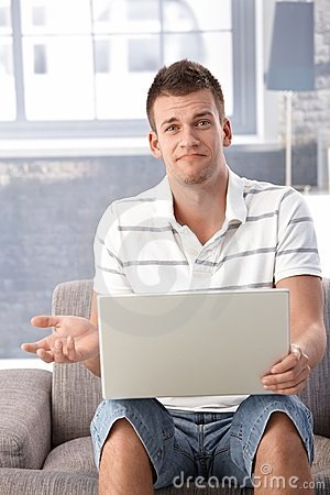 Unhappy man with laptop at home