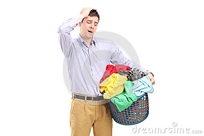 Unhappy man looking at a basket full of laundry