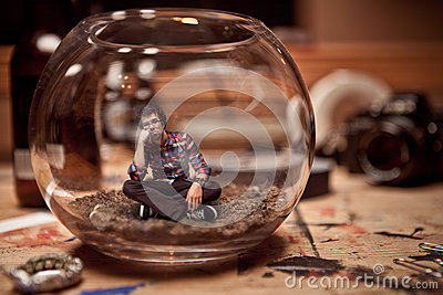 Unhappy Miniature man trapped inside a fishbowl.