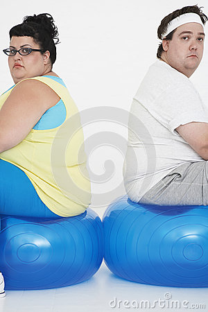 Unhappy Overweight Couple Sitting On Exercise Balls