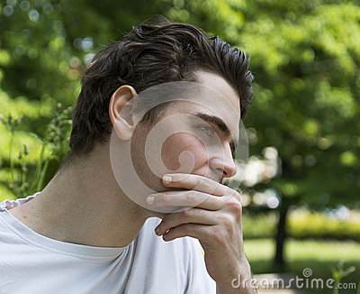 Unhappy, sad young man outdoors in park thinking