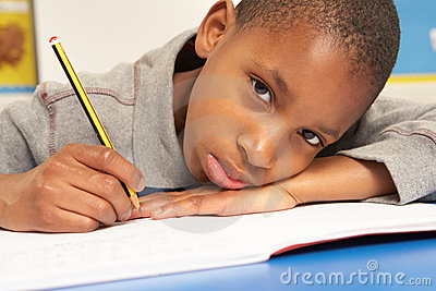 Unhappy Schoolboy Studying In Classroom