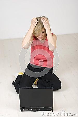Unhappy senior woman using laptop