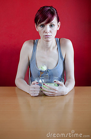 Unhappy skinny woman with her meal