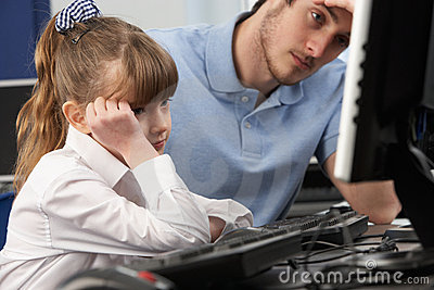 Unhappy teacher and girl using computer in class