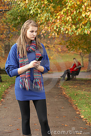 Unhappy Teenage Girl Standing In Autumn Park