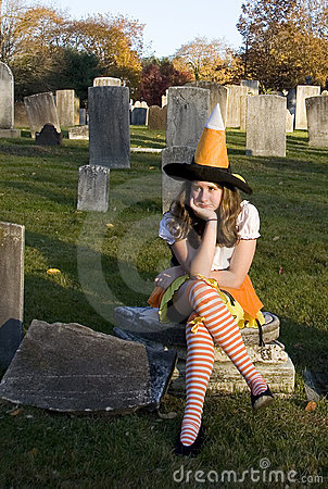 Unhappy Teenage Halloween Witch in Graveyard