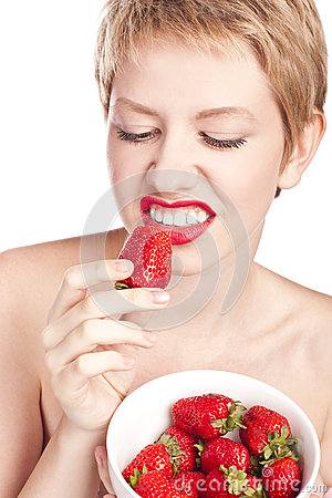 Unhappy woman eating strawberry. Studio