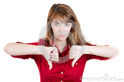 Unhappy woman giving thumbs down gesture looking with negative expression and disapproval