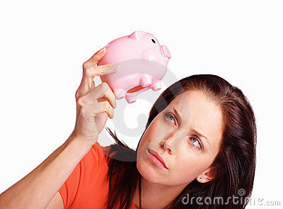 Unhappy woman looking for money in piggy bank